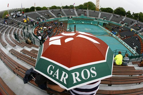 Spectators take shelter under an umbrella during the French Open tennis tournament on Monday May 26, 2008 at the Roland Garros stadium in Paris. Play at the French Open has been suspended because of rain on most courts.