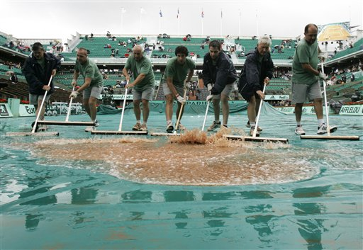 Workers remove water on center court after a rain delay at the French Open tennis tournament on Thursday May 29, 2008 at the Roland Garros stadium in Paris.
