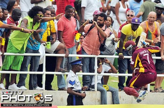 West Indies cricketer Marlon Samuels leaps over the billboard to shake hands with West Indies cricket star Chris Gayle.