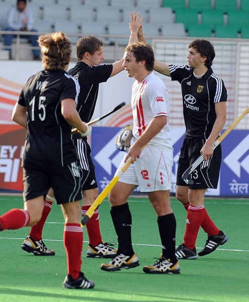 Canadian hockey player David Jameson watches as German hockey player Tobias Hauke celebrates a goal with teammates during their World Cup 2010 match at The Major Dhyan Chand Stadium in New Delhi. (AFP Photo)