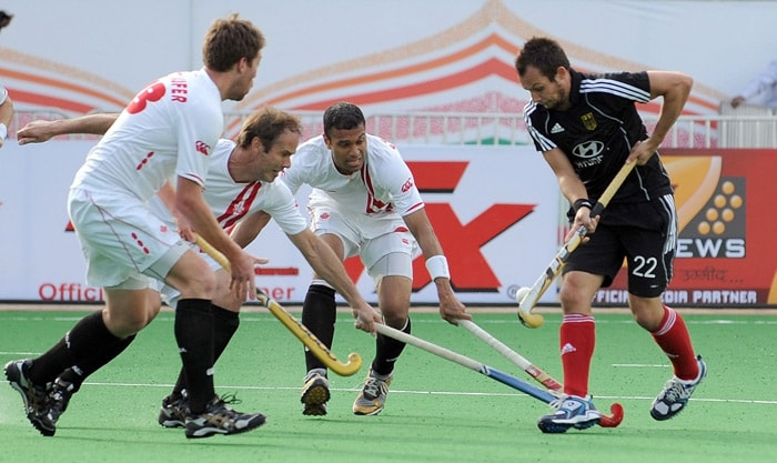 Canadian hockey players try to stop German hockey player Matthias Witthaus (R) during their World Cup 2010 match at the Major Dhyan Chand Stadium in New Delhi. (AFP Photo)
