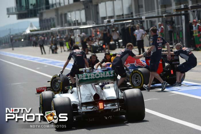 An errant wheel flew off Mark Webber's car during a pit-stop and struck a tv camerman in the back.