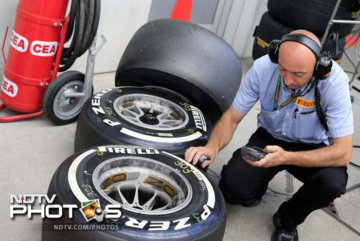 A Pirelli official performs tyre checks in the pits ahead of the qualifying session at the Nurburgring circuit.