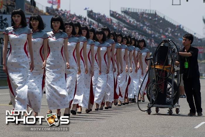 Of course, it has been widely known that the Chinese are very particular about hosting a sporting event.<br><br>A cleaner is seen walking alongside the grid girls - painting a contrast between hard-work and sheer grace. (AFP image)