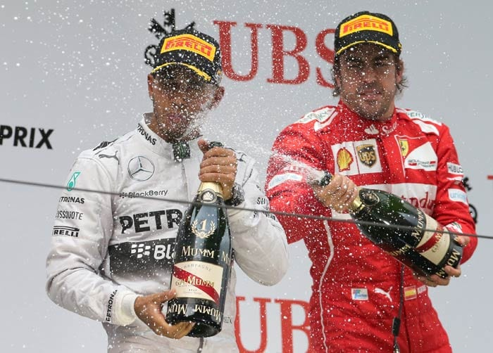 Fernando Alonso (right) joined the two Mercedes drivers for his first podium of the season.