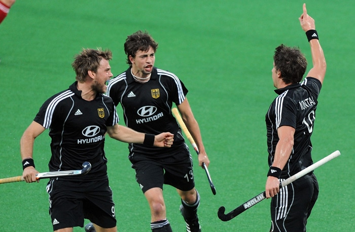 German hockey player Jan-Marco Montag (R) celebrates the first goal against England with Moritz Furste (L) and Tobias Hauke (C) during their World Cup 2010 semifinal match at the Major Dhyan Chand Stadium in New Delhi. (AFP Photo)