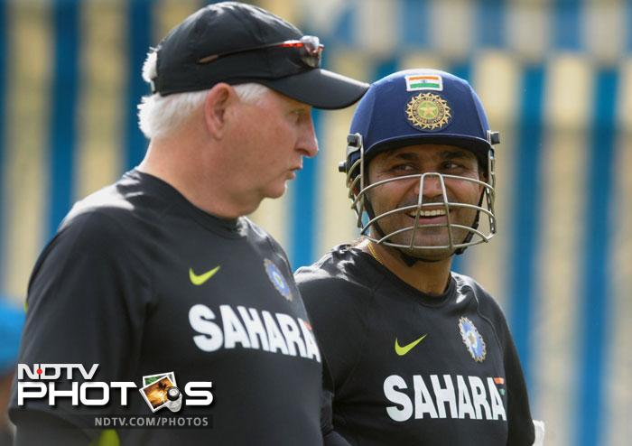 Virender Sehwag involved in a light chatter with coach Duncan Fletcher as the team practices.