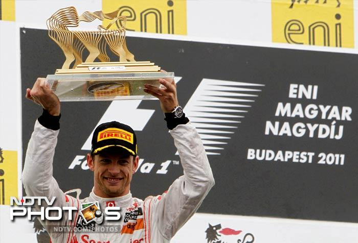 Jenson Button raises the trophy of the winner after the Hungarian Formula One Grand Prix at the Hungaroring circuit outside Budapest.