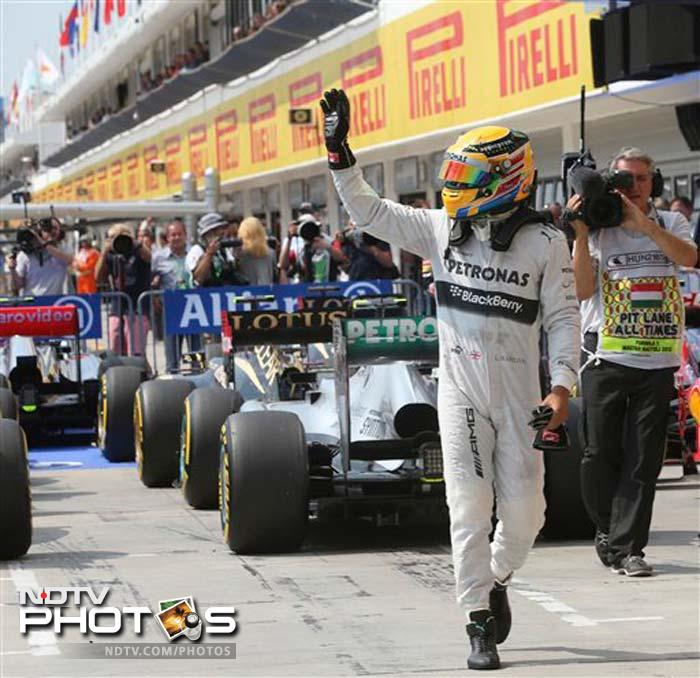 Lewis Hamilton waves to the crowd after achieving his fourth pole position of the season at Hungary. He clocked 1 minute, 19.388 seconds, just ahead of Sebastian Vettel's best lap of 1:19.426.