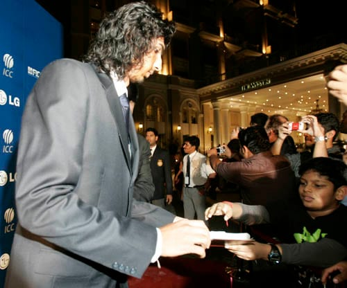 Indian cricket player Ishant Sharma, left, signs an autograph on the red carpet as he walks for the LG ICC Awards 2008 ceremony in Dubai.