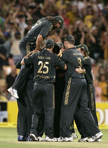 Andrew Symonds, left, jumps onto his huddled teammates after they defeated India in their one-day international cricket match at the Adelaide Oval on Sunday, February 17, 2008. Australia won by 50 runs after India are all out for 153.