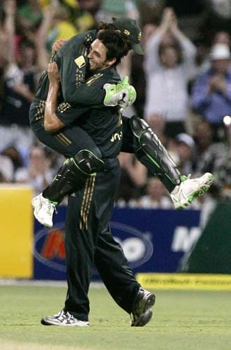 Adam Gilchrist, left, jumps into the arms of teammate Mitchell Johnson after they combined to take the wicket of Harbhajan Singh for 4 runs in their one-day international cricket match at the Adelaide Oval on Sunday, February17, 2008. Australia made 203 in their innings.