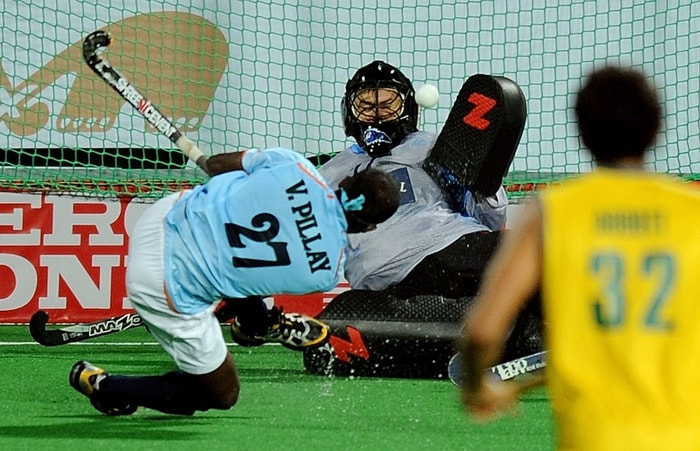 Indian hockey player Vikram Pillay (L) scores a goal past Australian goalkeeper Nathan Burgers (C) during their World Cup 2010 match at the Major Dhyan Chand Stadium in New Delhi. (AFP Photo)