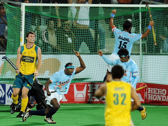 Indian hockey player Vikram Pillay (2L) celebrates after scoring against Australia during their World Cup 2010 match at the Major Dhyan Chand Stadium in New Delhi. (AFP Photo)
