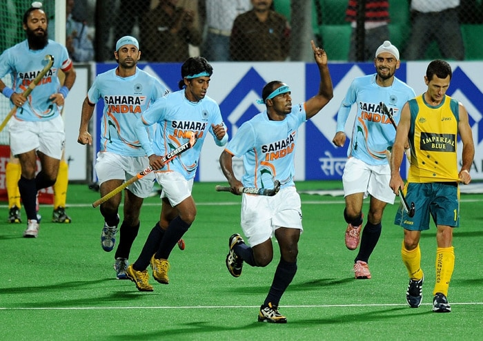 Indian hockey player Vikram Pillay (3R) celebrates after scoring a goal as Australian hockey player Jami Dwyer (R) looks on during their World Cup 2010 match at the Major Dhyan Chand Stadium in New Delhi. (AFP Photo)