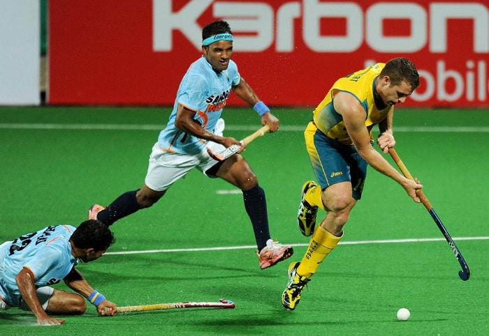 Australian field hockey player Grant Schubert (R) fights for the ball with Indian hockey players Dhananjay Mahadik (C) and Tushar Khandker (L) during their World Cup 2010 match at the Major Dhyan Chand Stadium in New Delhi. Australia beat India 5-2. (AFP Photo)