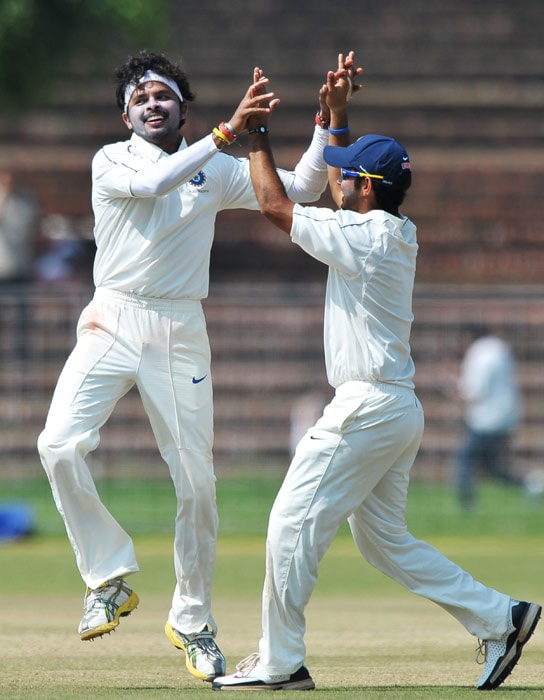 Santhakumaran Sreesanth and Piyush Chawla celebrate the wicket of during the second day of the three-day practice match between Australia and the Indian Board President's XI in Chandigarh. (AFP Photo)