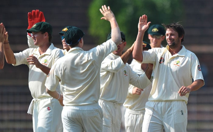 Ben Hilfenhaus celebrates with teammates the wicket of Ajinkya Rahane during the second day of the three-day practice match between Australia and the Indian Board President's XI in Chandigarh. (AFP Photo)