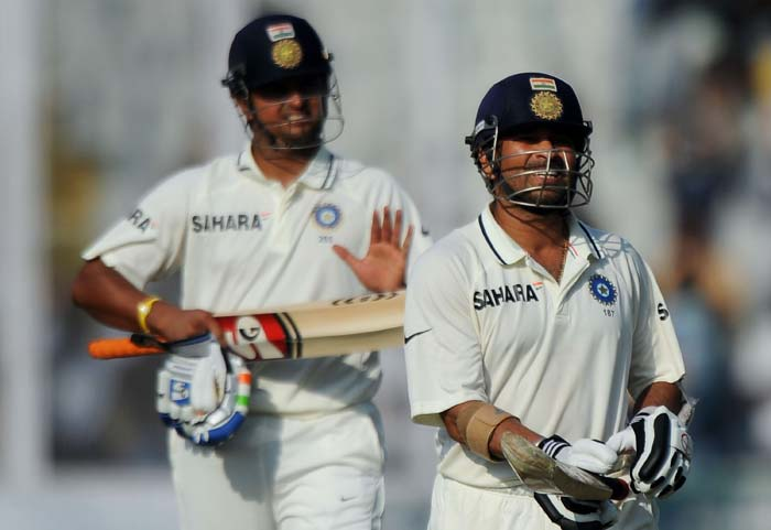 Sachin Tendulkar walks back to the dressing room after losing his wicket on his score of 98 runs, as teammate Suresh Raina applauds during the third day of the opening Test between India and Australia in Mohali. (AFP Photo)