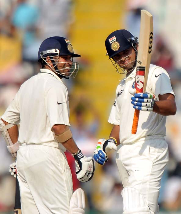 Sachin Tendulkar congratulates Suresh Raina for scoring a half-century during the third day of the opening Test between India and Australia in Mohali. (AFP Photo)