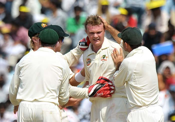 Australian cricketers congratulate bowler Doug Bollinger for taking the wicket of Rahul Dravid during the third day of the opening Test between India and Australia in Mohali. (AFP Photo)