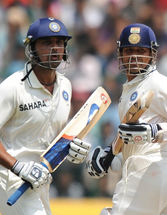 Sachin Tendulkar and Murli Vijay complete a run during the third day of the second Test between India and Australia at M. Chinnaswamy Stadium in Bangalore. (AFP Photo)