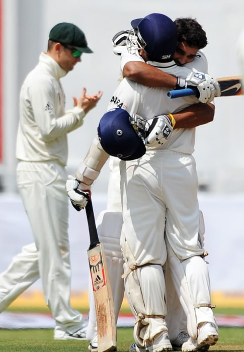Sachin Tendulkar congratulates teammate Murli Vijay (R) as Australia's Michael Clarke (L) claps after Vijay scored his century during the third day of the second Test between India and Australia at M. Chinnaswamy Stadium in Bangalore. (AFP Photo)