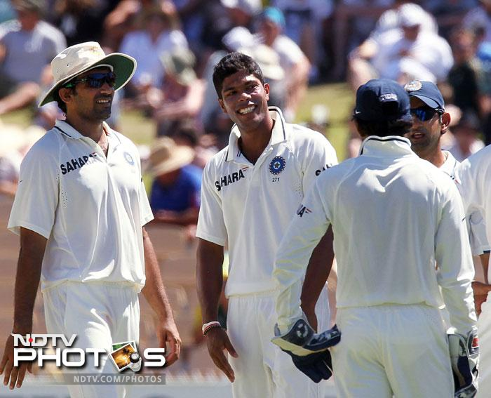 Umesh Yadav celebrates with his teammates after taking the wicket of Michael Clarke on Day 4 of the fourth Test match against Australia in the Border-Gavaskar Trophy Series at the Adelaide Oval. (AFP Photo)