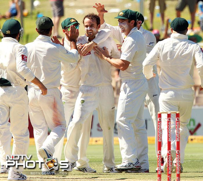 Australian players rush to spin bowler Nathan Lyon to congratulate him for taking the wicket of Sachin Tendulkar on Day 4 of the fourth Test match against India in the Border-Gavaskar Trophy Series at the Adelaide Oval. (AFP Photo)