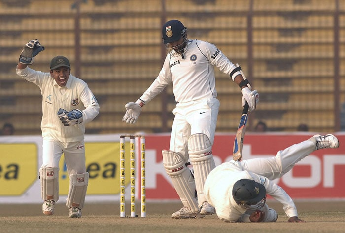 Raqibul Hasan takes a catch of Zaheer Khan as Mushfiqur Rahim runs during the first day of the first Test match between Bangladesh and India at Zohur Ahmed Chowdhury Stadium in Chittagong. (AFP Photo)