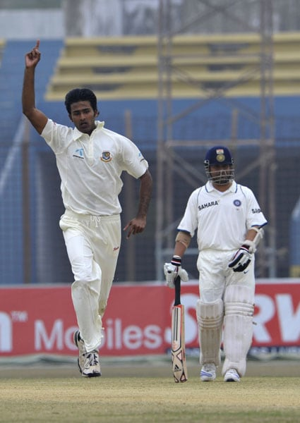 Shahadat Hossain celebrates after the dismissal of the unseen Ishant Sharma as his teammate Sachin Tendulkar (R) looks on during the second day of the first Test match between Bangladesh and India in Chittagong. (AFP Photo)