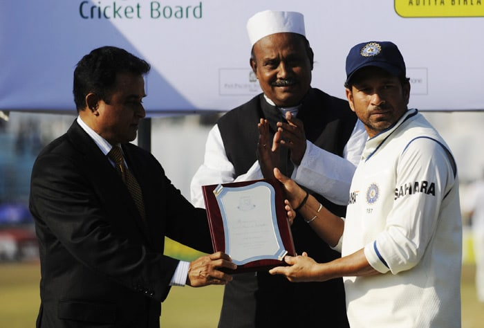 Sachin Tendulkar is gifted a crest from Bangladesh Cricket Board President Lotas Kamal for his 13,000 runs in his Test carrier as Chittagong Mayor AB, Mohiuddin looks on during the fifth day of the first Test match between Bangladesh and India in Chittagong. (AFP Photo)