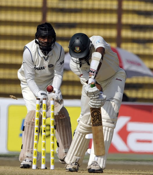 Shahadat Hossain is bowled by Amit Mishra as his teammate Dinesh Karthik looks on during the fifth day of the first Test match between Bangladesh and India in Chittagong. (AFP Photo)
