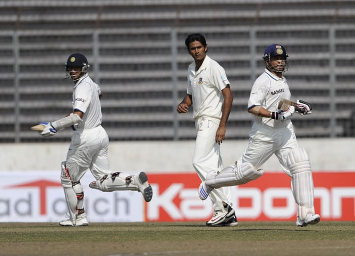 Sachin Tendulkar runs between the wickets with his teammate Rahul Dravid as Shahadat Hossain looks on during the second day of the second Test match against Bangladesh at The Sher-e Bangla National Stadium in Dhaka. (AFP Photo)