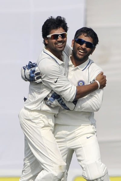 Mahendra Singh Dhoni and teammate Murali Vijay celebrate the dismissal of Mohammad Mahmudullah during the fourth day of the second Test match in Dhaka. (AFP Photo)