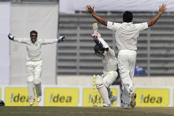 Mahendra Singh Dhoni and his teammate Zaheer Khan celebrate the dismissal of Raqibul Hasan during the fourth day of the second Test match in Dhaka. (AFP Photo)
