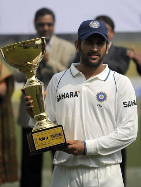 Indian captain Mahendra Singh Dhoni holds the Test series trophy at the end of the second Test match between Bangladesh and India in Dhaka. (AFP Photo)