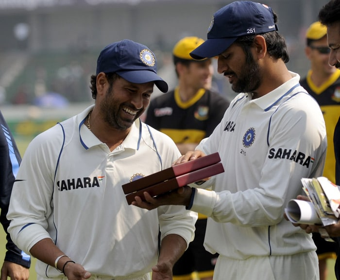 Mahendra Singh Dhoni holds the award which teammate Sachin Tendulkar received for completing 13,000 runs in his Test career after the fourth day of the second Test match in Dhaka. (AFP Photo)
