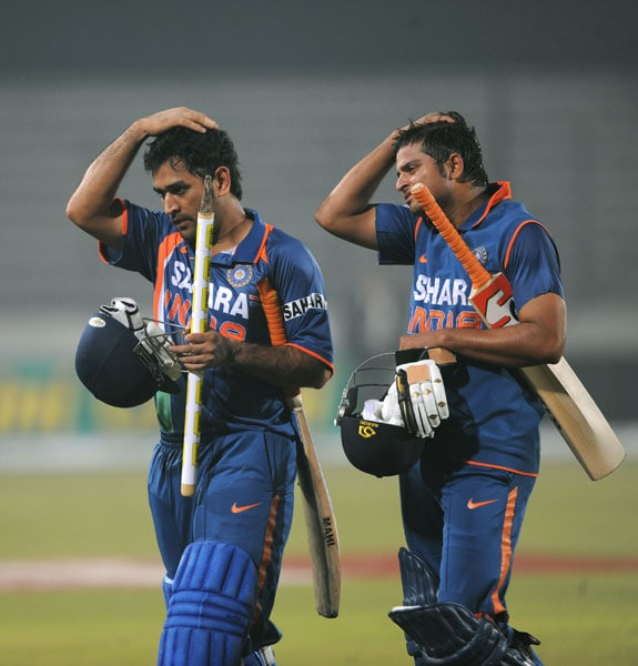 Mahendra Singh Dhoni and teammate Suresh Raina walk off the pitch after victory over Bangladesh in the third ODI of the tri-series in Dhaka. (AFP Photo)