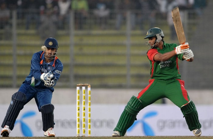 Mahendra Singh Dhoni looks on as Mahmudullah Riyad plays a stroke during the third ODI of the tri-series in Dhaka. (AFP Photo)