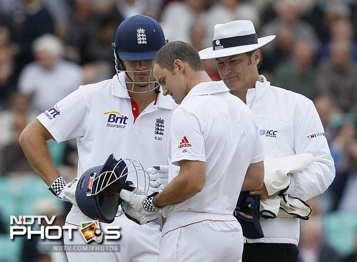Andrew Strauss looks at his damaged helmet with Alastair Cook and umpire Simon Taufel after it was hit by a ball off the bowling of Ishant Sharma in the fourth Test at The Oval Cricket Ground in London. (AP Photo)