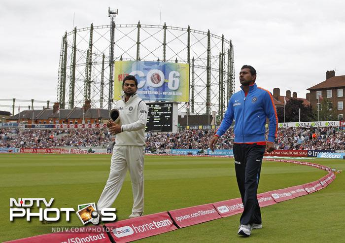 Praveen Kumar walks around the boundary as he speaks with Virat Kohli during the first day of the fourth Test between England and India at The Oval Cricket Ground in London after missing the game because of an injury. (AFP Photo)
