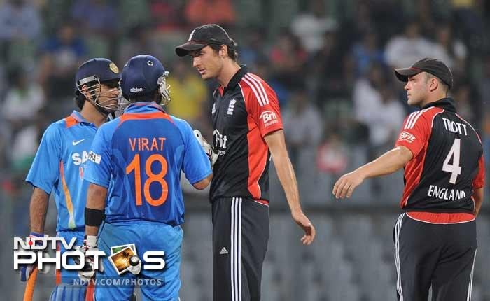 Virat Kohli and captain Mahendra Singh Dhoni speak with Steven Finn as teammate Jonathan Trott tries to pull him back during the fourth One-Day International between India and England at the Wankhede stadium in Mumbai. England were 220 all out after 47 overs. (AFP Photo)