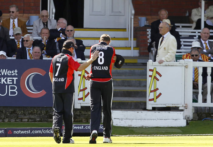 Ian Bell assists teammate Stuart Broad as he leaves the field holding his arm after bowling during the fourth ODI between England and India at Lord's in London. (AFP Photo)