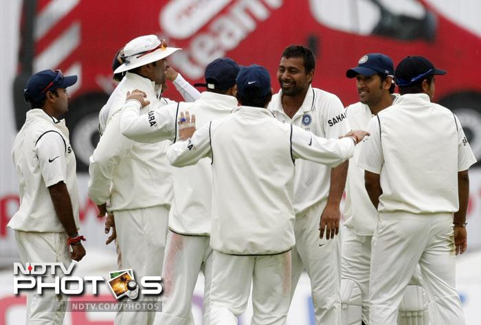 Praveen Kumar is congratulated by teammates after taking the wicket of Ian Bell on the second day of the third Test match at the Edgbaston Cricket Ground, Birmingham. (AP Photo)