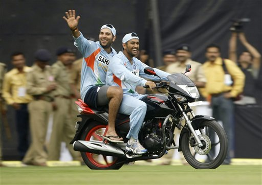 Yuvraj Singh, left, rides pillion as Mahendra Dhoni drives the motorcycle that Yuvraj won as an award for Man of the Match in the second one-day international match between India and England in Indore on Monday, November 17, 2008. Yuvraj Singh hammered England's attack for his second successive century and then returned to snare four wickets that propelled India to a 54-run victory in the second limited-overs international.(AP Photo)
