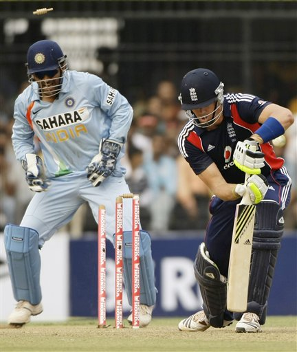 Mahendra Singh Dhoni, left, looks on as England captain Kevin Pietersen is dismissed during the second one-day international match between India and England in Indore on Monday, November 17, 2008. (AP Photo)
