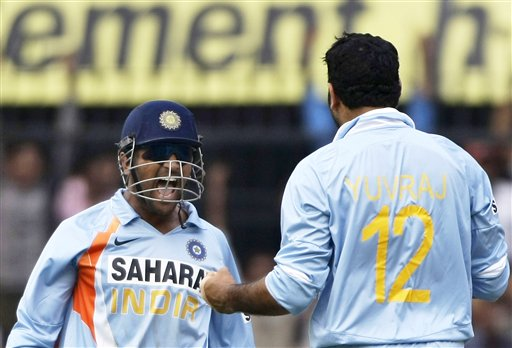 Yuvraj Singh, right, and Indian captain Mahendra Dhoni, left, celebrate after Yuvraj dismissed England batsman Andrew Flintoff, unseen, during the second one-day international cricket match between India and England in Indore on Monday, November 17, 2008. (AP Photo)
