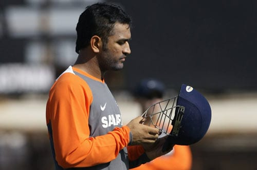 Indian team captain MS Dhoni prepares to don his helmet before a session at the nets in Rajkot on Thursday. (AP Photo)