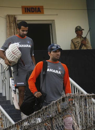 Indian players Zaheer Khan and Yuvraj Singh arrive for a practice session as an armed security person keeps watch in Rajkot on Thursday. (AP Photo)